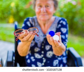 Pensioner woman with hard choice between contact lens and eye glass.