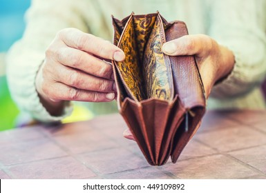 Pensioner woman holding in hands wallet without money.