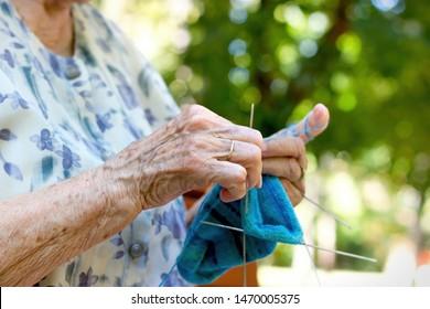 Pensioner woman knitting socks for her grandchildren, retiree lifestyle concept, enjoys in retirement