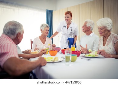 Pensioners at lunch with nurse in the retirement house