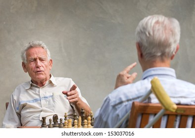 Pensioners talking and playing chess in courtyard