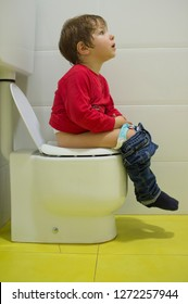 Pensive 3 years boy using ceramic children toilet. Adapted small size bowl
