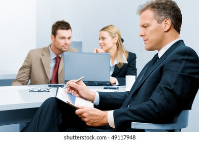 Pensive absorbed mature businessman working on growing chart with colleagues in background
