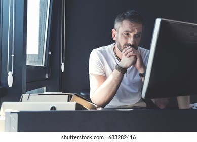 Pensive adult man is sitting at his desk