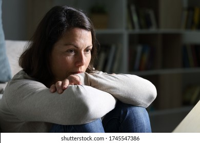 Pensive adult woman looking away thinking sitting on the floor in the livingroom at night at home