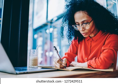 Pensive African American businesswoman writing down notes of financial report sitting at laptop computer and working remotely in coffee shop.Dark skinned female planning organization process