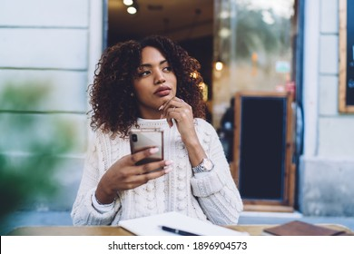 Pensive African American female in casual clothes sitting at wooden table with copybook and browsing mobile phone while resting in cafe