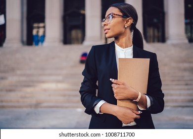 Pensive African American female lawyer in stylish formal suit holding folder with mock up area and looking away standing against courthouse. Half length of woman professional advocate with documents