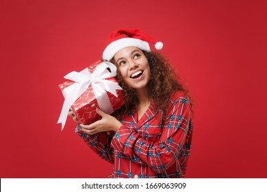 Pensive african american girl in pajamas homewear Christmas hat rest at home isolated on red background. Relax good mood lifestyle concept. Mock up copy space. Hold present box with gift ribbon bow