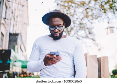 Pensive african american hipster guy in trendy hat installing application on smartphone spending time outdoors,thoughtful dark skinned man in shirt with copy space for brand name reading news on phone