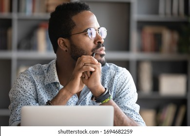 Pensive African American man in glasses distracted from computer work look in distance thinking or pondering, thoughtful biracial male lost in thoughts make plans visualizing, business vision concept