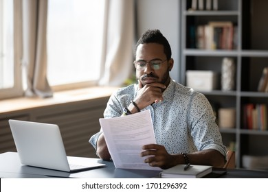 Pensive African American man sit at desk working on laptop reading paper document thinking or analyzing, thoughtful biracial male worker consider paperwork agreement at office or home workplace - Shutterstock ID 1701296392