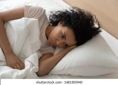 Pensive african American millennial girl lying on soft pillow suffering from insomnia having sleep deprivation, thoughtful black young woman relaxing in white bed pondering thinking in bedroom