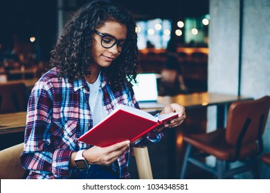 Pensive African American student with curly hair reading interesting bestseller during free time in library.Smart dark skinned teen in eyeglasses studying at book to preparing for exam in school