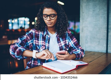 Pensive African American student in eyewear looking at wristwatch to managing time during studying at book in library.Dark skinned hipster girl tracking time on smartwatch during reading textbook