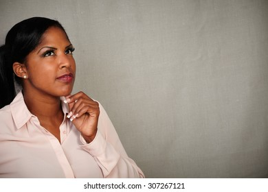Pensive african woman thinking with hand on chin while standing against grey texture background