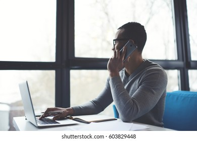 Pensive afro american male freelancer looking out window sitting at table with laptop resting from hard working day having mobile conversation from executive manager reporting about fulfilling tasks