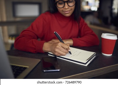 Pensive afro american student in eyeglasses writing ideas in diary while doing homework in cafe, skilled businesswoman planning working process creating to-do list for startup noting points goals