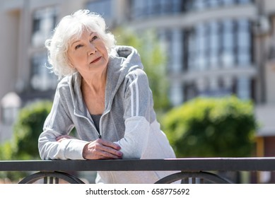 Pensive aged woman resting near pavement fence