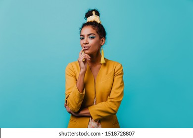 Pensive amazing african girl looking to camera. Indoor portrait of curious lovely woman wears elegant yellow jacket.