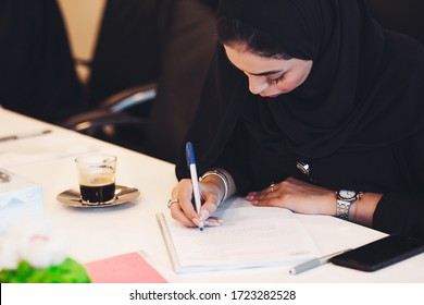 Pensive Arab woman planning working schedule writing in notebook while sitting at working place, Arabic female administrative manager making notes of information browsed on netbook.