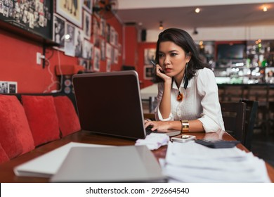 Pensive Asian bar owner using laptop to pay bills online