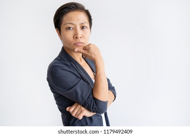Pensive Asian business woman touching chin with fingers. Young lady looking at camera. Contemplation concept. Isolated view on white background.