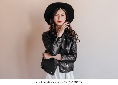 Pensive asian young woman in hat looking at camera. Japanese girl in leather jacket standing on beige background.