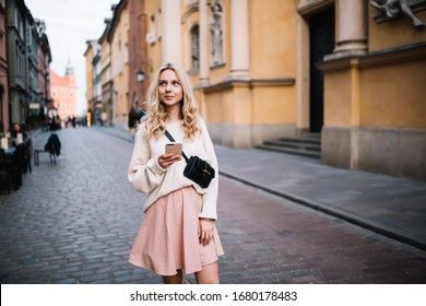 Pensive attractive blonde in stylish skirt carrying belt bag and browsing mobile phone while strolling on old town street looking around