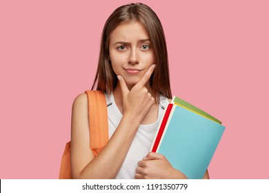 Pensive attractive Cauasian girlfriend holds chin and looks with puzzlement, has straight hair, carries rucksack with school object, holds textbooks, poses against pink background. Studying concept