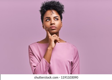 Pensive attractive curly African American female being deep in thoughts, raises eye, wears fashionable clothes, stands against lavender wall.