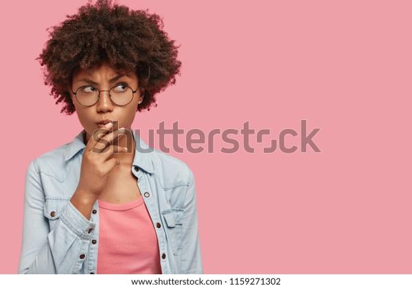 Pensive attraktive, lockig afrikanische Frau, die tief in Gedanken ist, hebt Augenbrauen, kurbelt Lippen, hält Kinn, trägt modische Kleidung, steht gegen rosafarbene Wand mit Kopienraum für Ihren Text