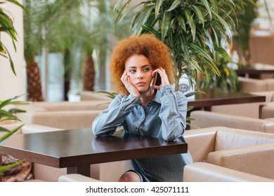 Pensive attractive curly young woman talking on cell phone at the table in cafe