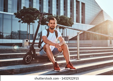 Pensive attractive man is sitting on the stairs with his electric scooter at bright sunny day.