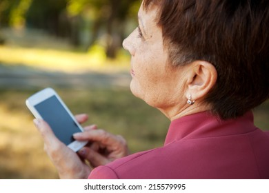 pensive attractive woman 50 years with mobile phone in hand