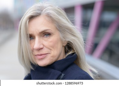 Pensive attractive woman with shoulder length blond hair scrutinising the camera with a quiet smile as she stands on an outdoor walkway in town in a close up portrait
