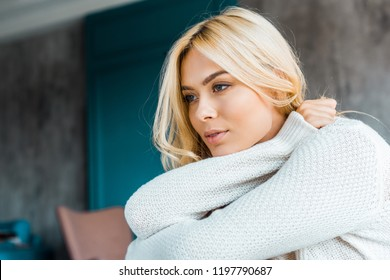 pensive attractive woman in sweater looking away in bedroom in morning