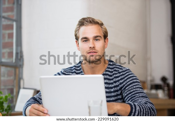 Pensive attractive young young man sitting at his laptop staring at the camera with a serious contemplative expression