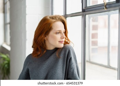 Pensive attractive young redhead woman standing leaning on the sill staring out of a window