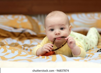 The pensive baby boy sucking a brown beads on the bed