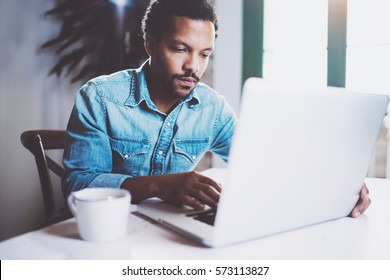 Pensive bearded African man working at home while sitting the wooden table.Using modern laptop for new job search.Concept of young people work mobile devices.Blurred background.Crop