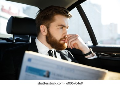 Pensive bearded business man which sitting in car with newspaper in hand while looking at window