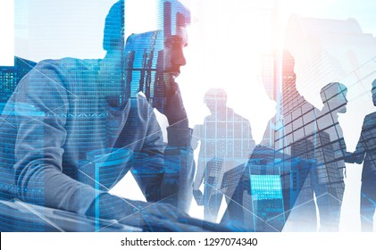 Pensive bearded businessman working with laptop with his colleagues silhouettes behind him with double exposure of city. Toned image