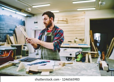 Pensive bearded male carpenter holding wooden brick pondering ideas for making craft detail, owner of wooden manufacture business thinking about furniture construction standing near working place