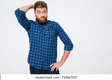 Pensive bearded man looking up and don't know what to do isolated over white