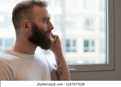 Pensive bearded man talking on phone and looking out window. Serious young man with tattoo considering plan. Communication concept