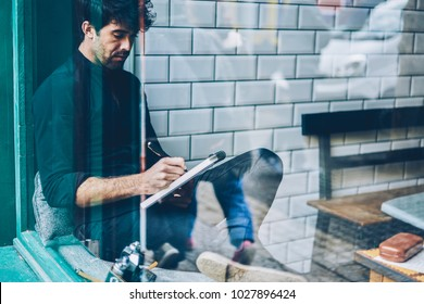 Pensive bearded young man dressed in black shirt writing down essay in notepad resting in coffee shop interior.Skilled hipster guy writer noting some records in notebook sitting in coworking space