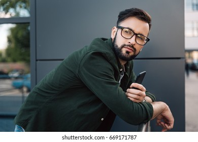 pensive bearded young man in eyeglasses holding smartphone