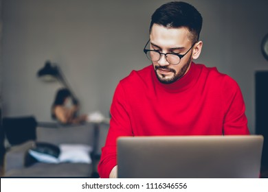 93484c75fd Pensive bearded young man in stylish eyeglasses for provide eyes protection  working on freelance at modern