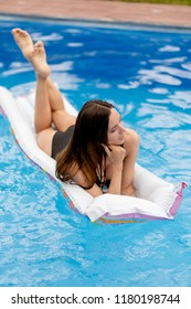 pensive beautiful girl is lying on the inflatable air bed. relaxation, lifestyle, travel concept